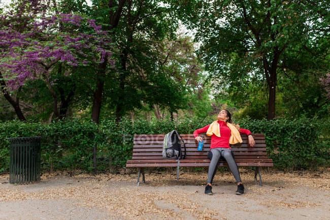 Sportive girl with bottle of water and towel on shoulders resting on bench in park — Stock Photo