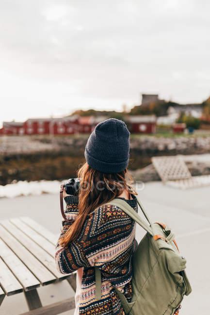 Vue arrière de la femme avec sac à dos, tenant la caméra et prendre des photos — Photo de stock