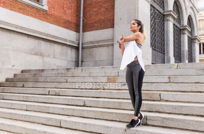 Sportive woman warming up shoulder on stairs at street — Stock Photo