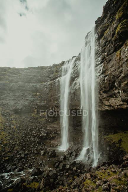 Живописный пейзаж захватывающий водопад потока в скалах — стоковое фото