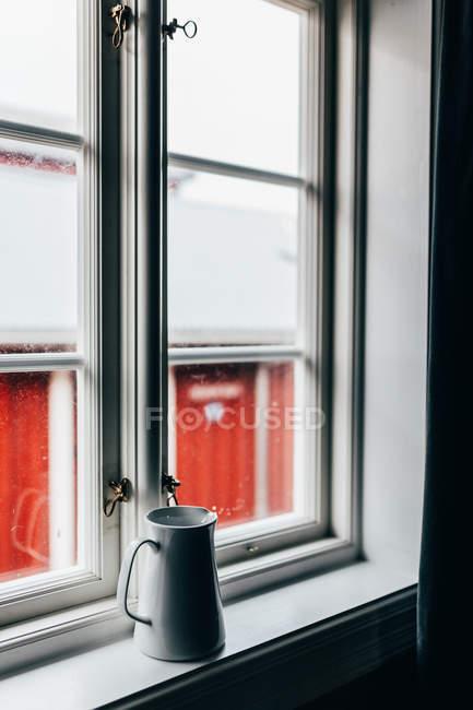 Weiße Keramik Krug auf weißen Fensterbank auf Grund des roten Hauses hinter Fenster. — Stockfoto