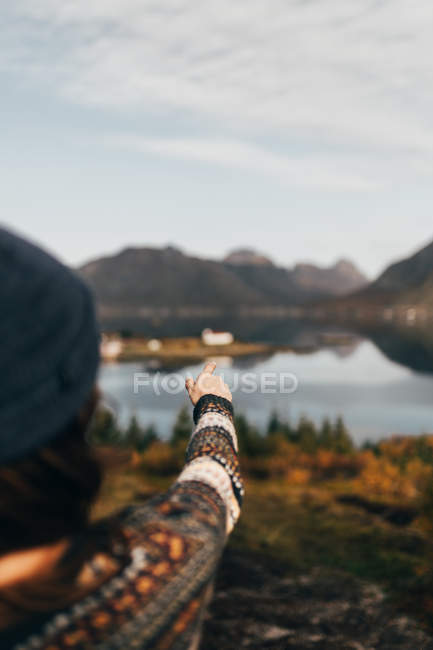 Over shoulder view of woman pointing away at lake in mountains. — Stock Photo