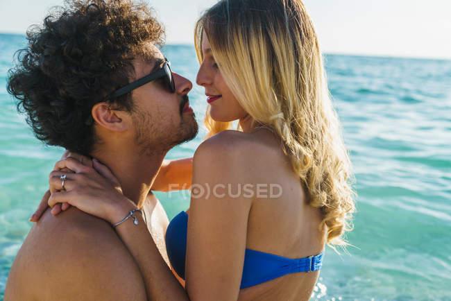 Vue de côté d'embrasser le couple posant dans l'eau des Océans — Photo de stock