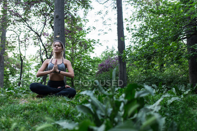 Sporty girl sitting on ground and performing yoga asana among woods — Stock Photo