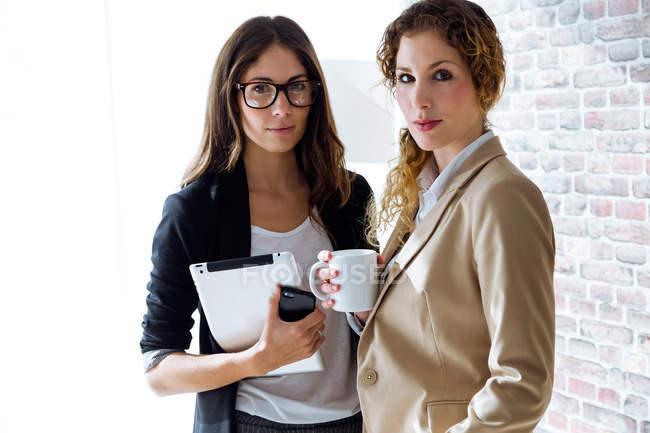 Портрет двух предпринимателей, глядя на камеру во время кофе-брейк в офисе — стоковое фото