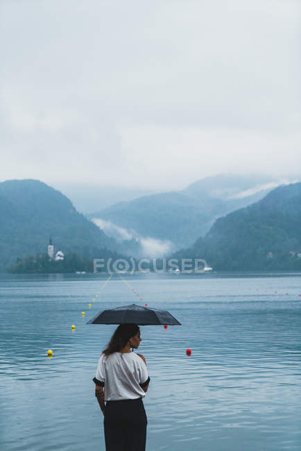 Rear view of brunette woman posing with umbrella and looking over shoulder on lake shore — Stock Photo
