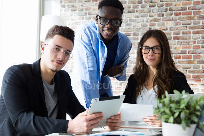 Portrait of group of business people looking at camera in modern office. — Stock Photo