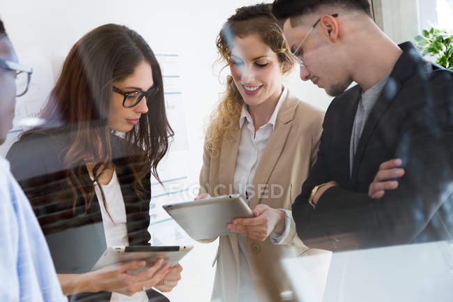Group of business people looking at colleagues tablet at modern office. — Stock Photo