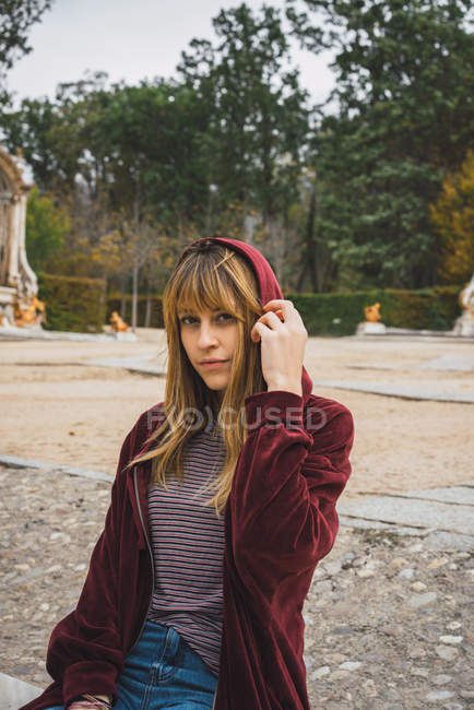 Jeune fille brune en hoodie rouge posant au parc — Photo de stock