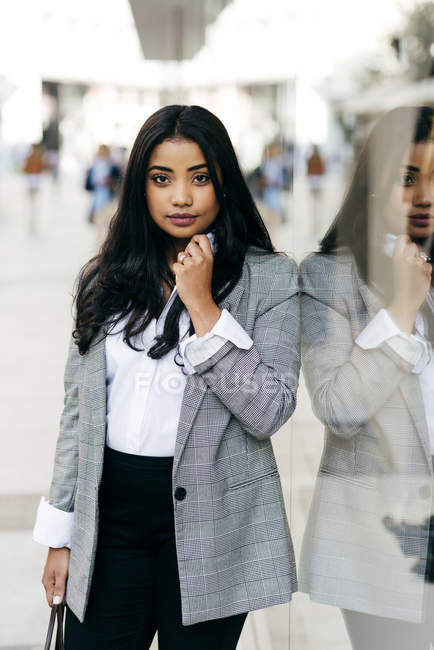 Woman posing near shop window and looking at camera — Stock Photo