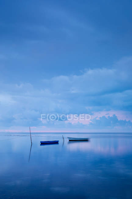Boats floating in calm sea reflecting cloudscape — Stock Photo