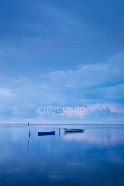 Bateaux flottant en mer calme reflétant cloudscape — Photo de stock