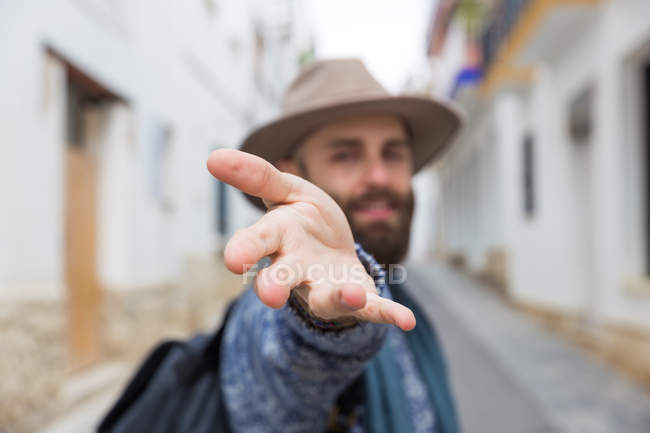 Bearded man in hat looking at camera and gesturing follow me — Stock Photo