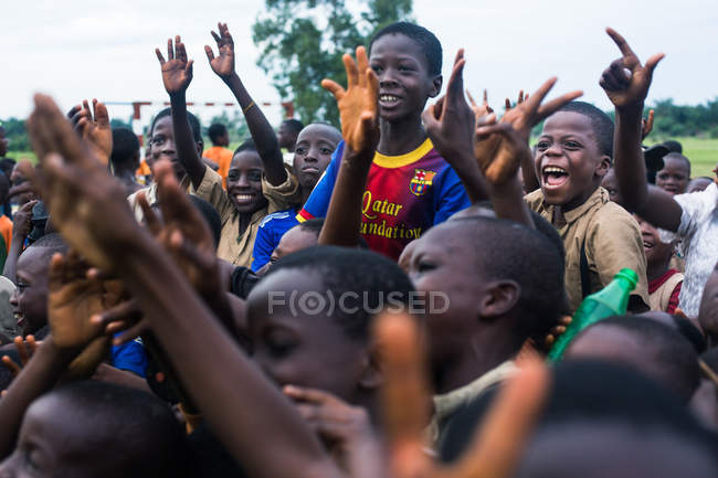 BENIN, AFRICA - AUGUST 31, 2017: Cheerful African children yelling and gesturing with hands up — Stock Photo