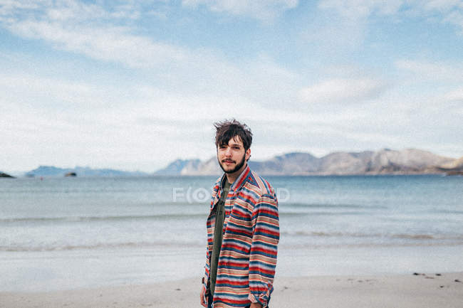 Portrait of man posing at mountain lake sand shore and looking at camera — Stock Photo