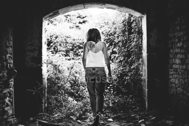 Vista posteriore della donna che cammina in rovine di mattoni contro la luce . — Foto stock