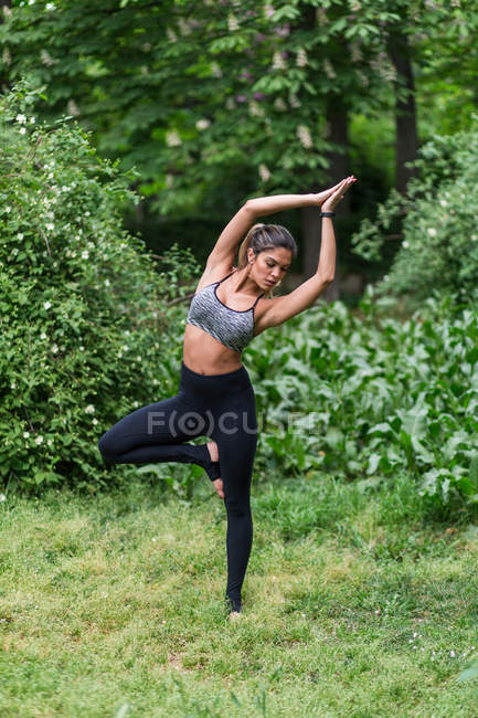 Concentrated woman performing yoga asana and meditating in park — Stock Photo