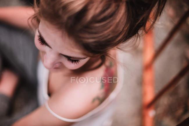 Draufsicht auf Frauen mit tätowiertem Rücken, die sitzen und zur Seite schauen — Stockfoto