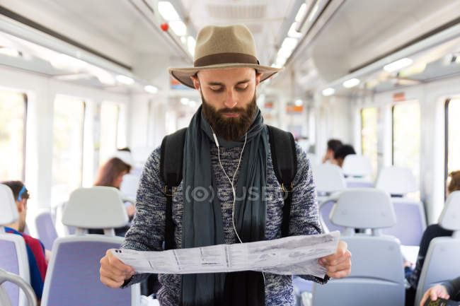 Bearded tourist with headphones and reading map at public train. — Stock Photo