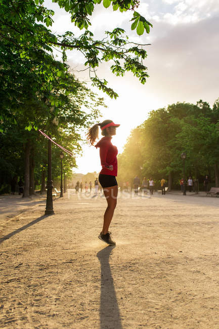 Side view of girl jumping with jump rope at park — Stock Photo