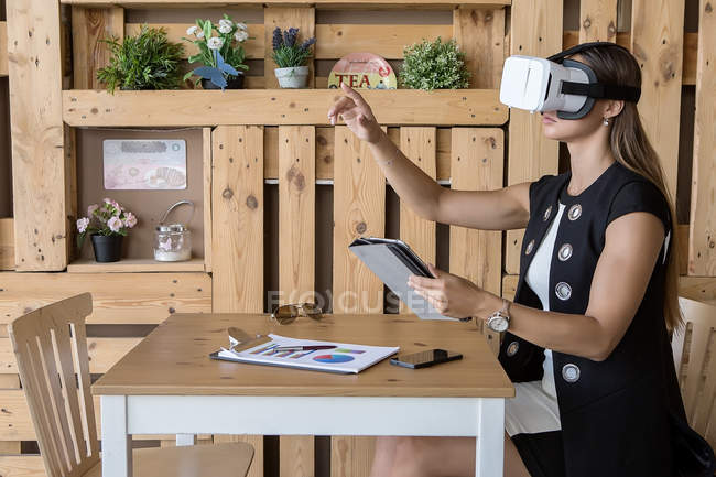Side viwe of girl sitting at cafe table and posing in VR headset — Stock Photo