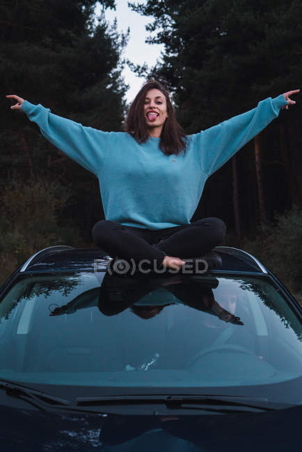 Brunette girl in blue sweatshirt sitting on top of car with raised aside arms and showing tongue at camera — Stock Photo