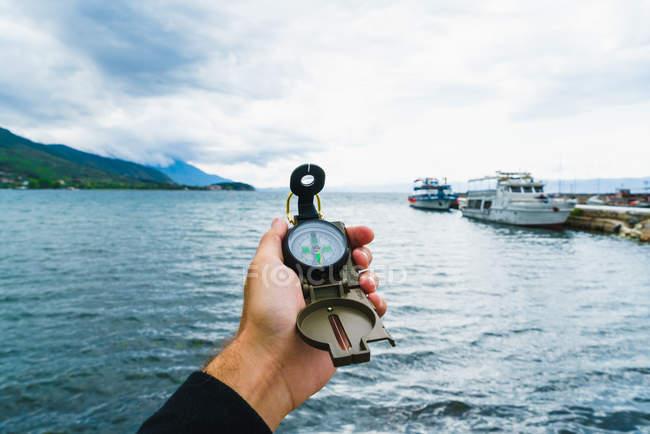 Bussola di tenuta mano maschio raccolto sopra marine con barche ormeggiate — Foto stock
