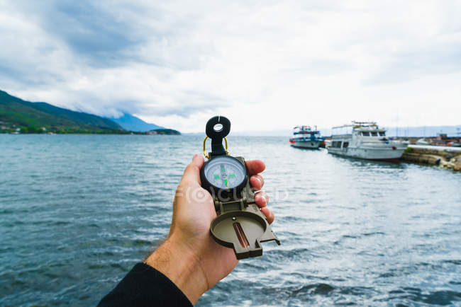 Crop male hand holding compass over marine with moored boats — Stock Photo