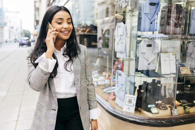 Retrato de mulher elegante vestindo casaco falando no smartphone e andando ao longo de vitrines na rua — Fotografia de Stock