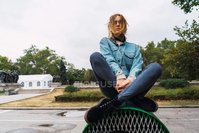 Stylish girl sitting on ventilation with legs crossed — Stock Photo