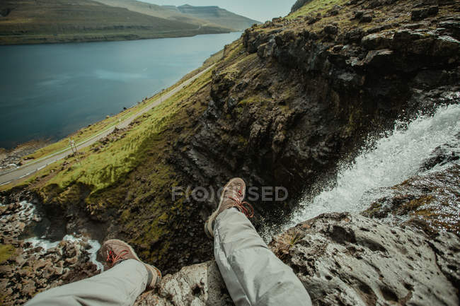Looking down view of male sitting on cliffs edge over rapid mountain stream — Stock Photo