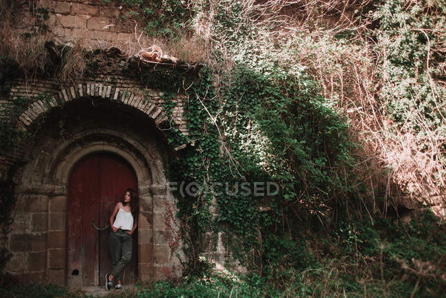 Woman posing under door archway of medieval building with ivy covered wall — Stock Photo