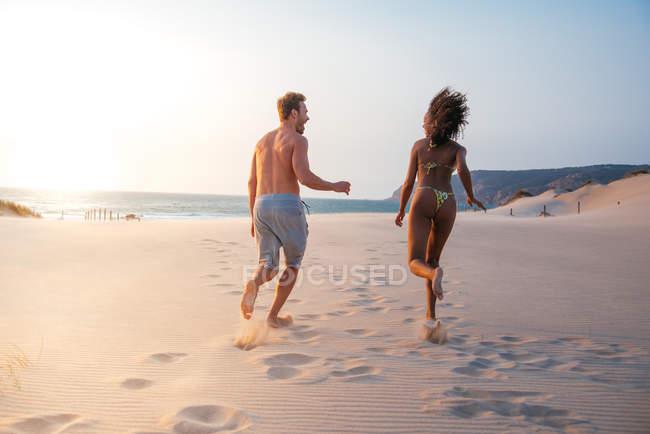 Vista posteriore della coppia felice allegramente in esecuzione sulla spiaggia tropicale romantica — Foto stock
