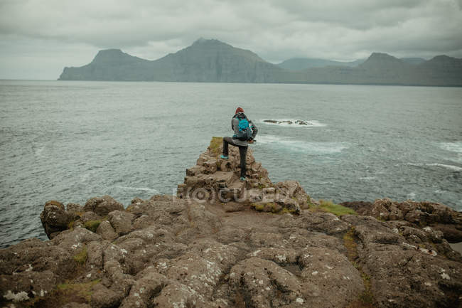 Rear view of traveler with backpack posing on rocks over ocean bay — Stock Photo