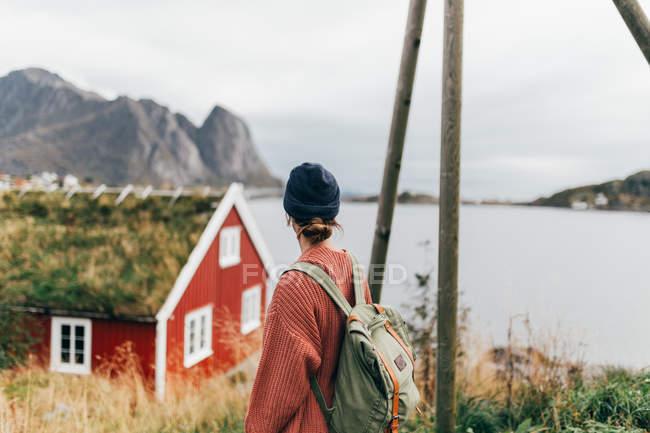 Rückansicht der Frau des Hauses mit Grasdach über Bergsee genießen — Stockfoto