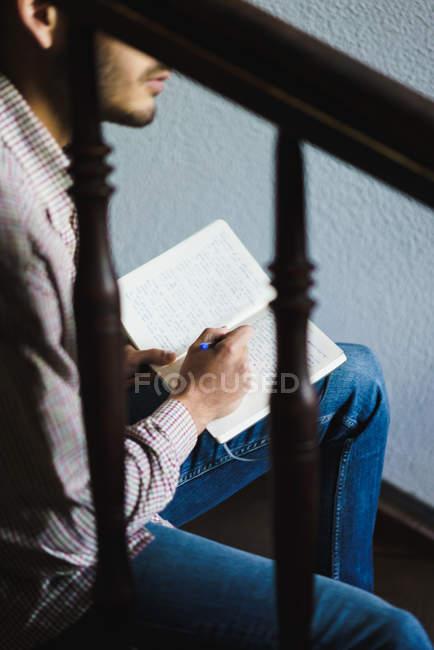 Боковой вид неузнаваемого человека, сидящего на лестнице и пишущего в блокноте . — стоковое фото