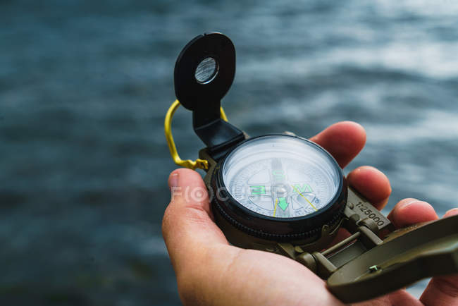 Crop male hand holding compass over sea waves — Stock Photo