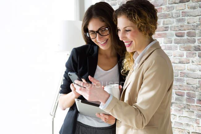 Портрет двух улыбающихся бизнесвумен, смотрящих на смартфон в лофт-офисе . — стоковое фото