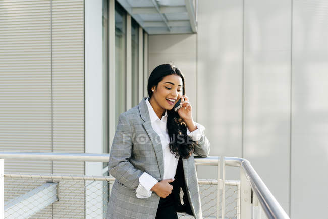Laughing businesswoman in jacket talking on phone at balcony of business building — Stock Photo