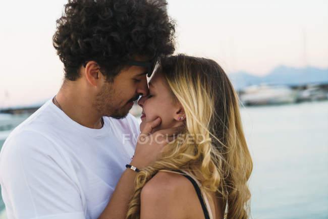 Porträt eines jungen Paares beim Kuscheln auf der Seebrücke — Stockfoto