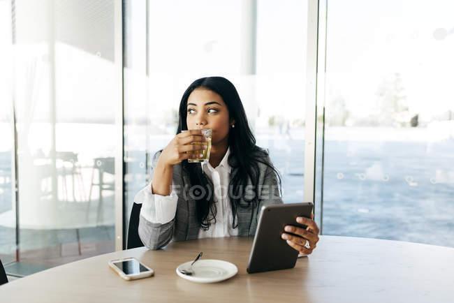 Ritratto di donna d'affari con tablet che beve tè e guarda da parte — Foto stock
