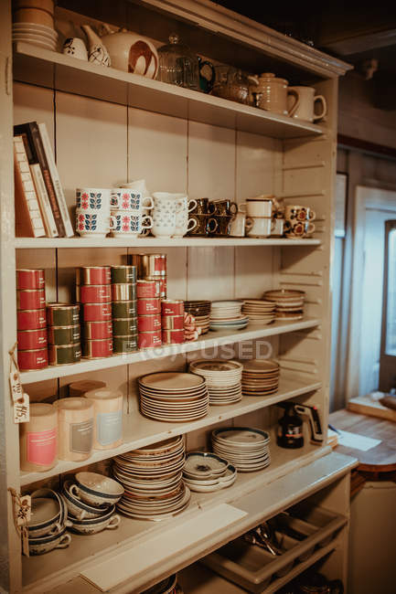 Wooden shelves with dinnerware at kitchen — Stock Photo
