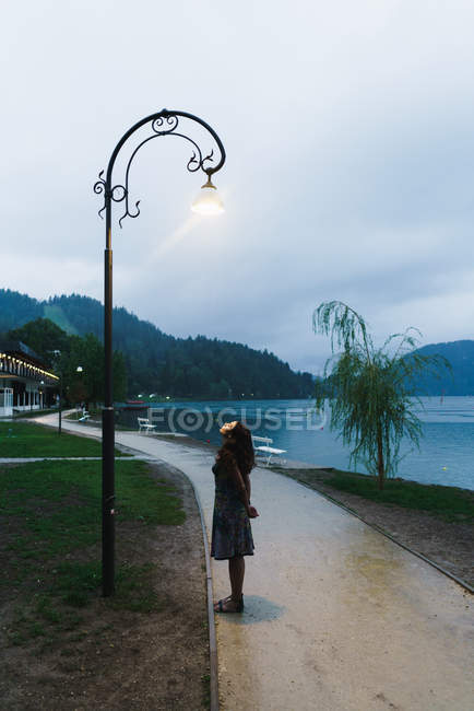 Side view of woman standing at park alley and looking up on lamppost — Stock Photo