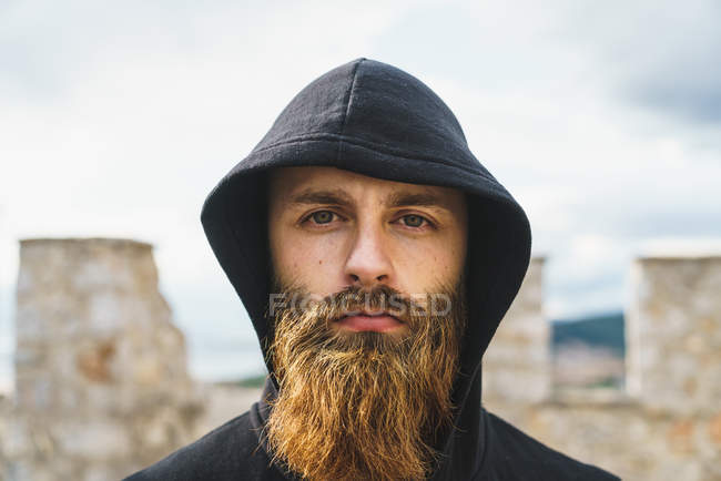 Portrait of young man with beard in black hood posing looking at camera. — Stock Photo
