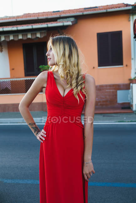 Portrait of blonde woman with hairstyle posing in red evening dress at urban scene and  looking away — Stock Photo