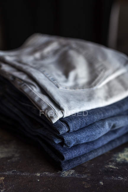 Stack of blue jeans pants on dark table. — Stock Photo