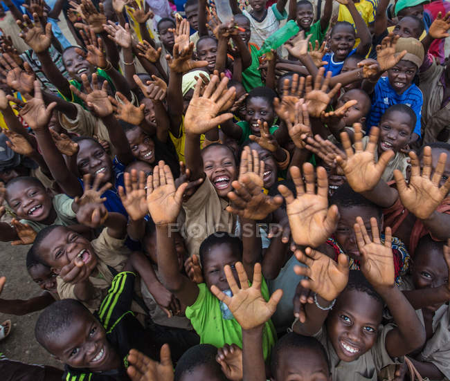 BENIN, AFRICA - AUGUST 30, 2017: Low angle of smiling black children crowd gesturing greeting with hands up and looking at camera. — Stock Photo