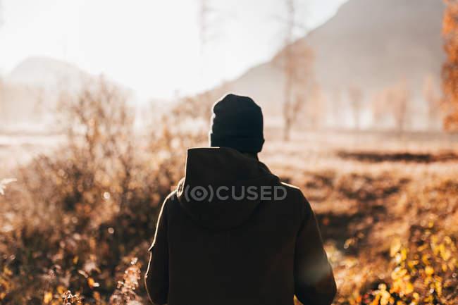 Rückansicht der Mann zu Fuß auf der Landstraße auf Land — Stockfoto