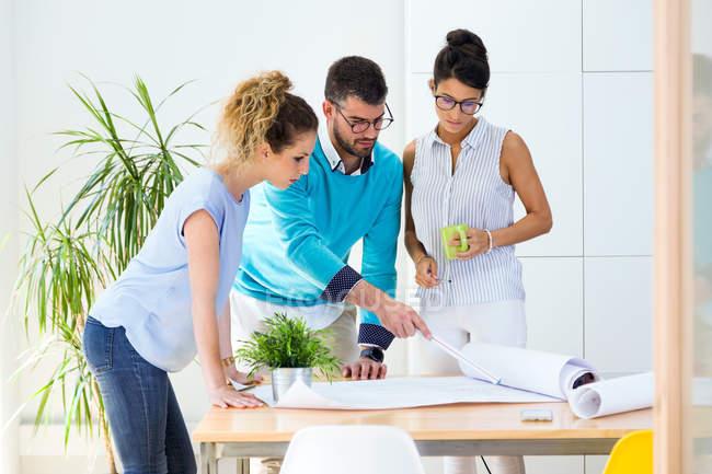 Gruppo di uomini d'affari che guardano le carte sul tavolo in ufficio moderno . — Foto stock