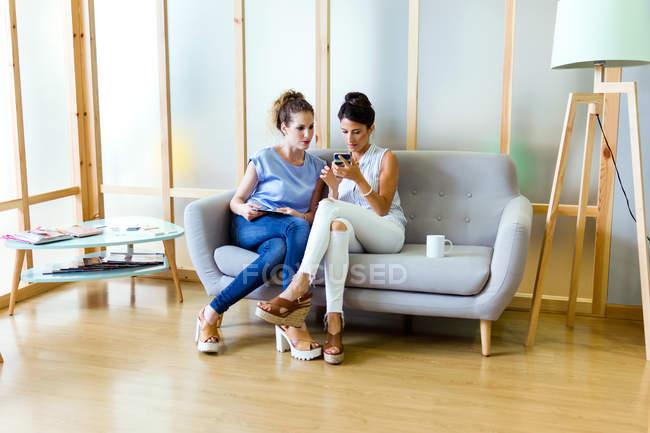 Портрет двух деловых женщин, сидя на тренер и просмотра смартфон — стоковое фото